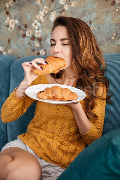 Portrait of a smiling attractive woman eating croissant Stock photo © deandrobot
