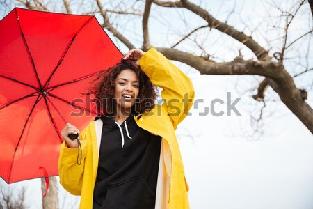 Happy african curly young woman wearing yellow coat Stock photo © deandrobot