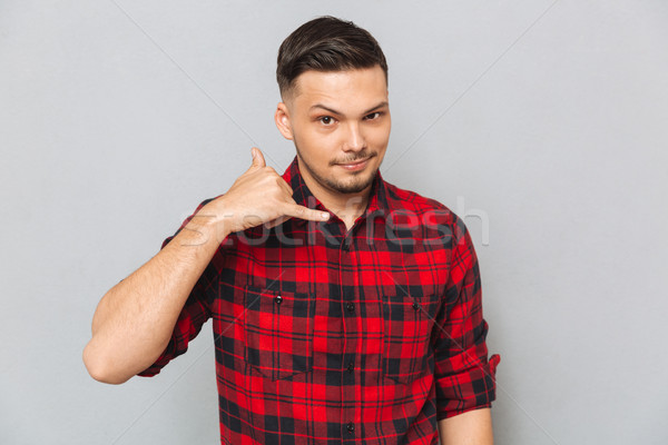 Young man in shirt showing phone sign Stock photo © deandrobot