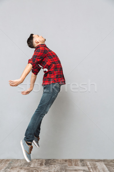 Concentrado moço saltando cinza parede foto Foto stock © deandrobot