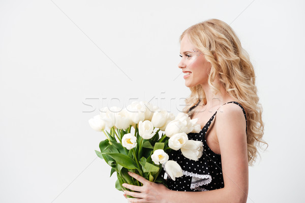 Side view of woman posing with bouquet flowers Stock photo © deandrobot
