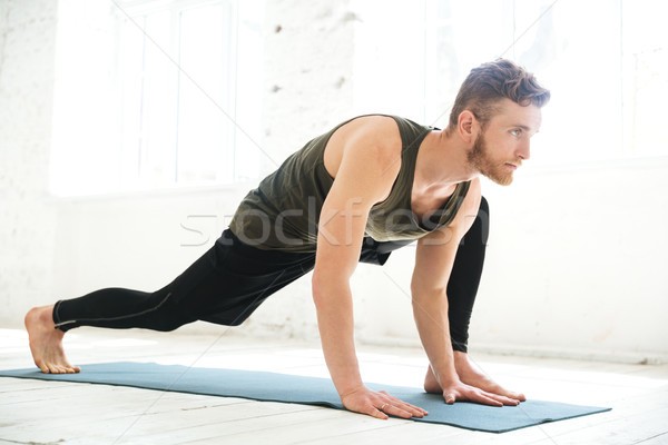 Handsome concentrated man doing yoga on mat Stock photo © deandrobot