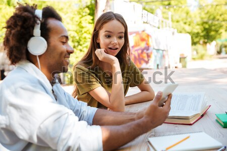 Side view of two smiling young friends sitting by table Stock photo © deandrobot