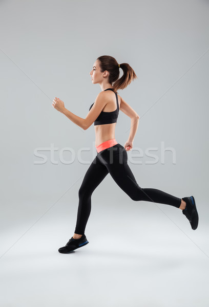 Stock photo: Full length picture of a sports woman running in studio