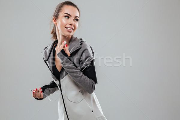Glimlachend vrouwelijke runner warm kleding luisteren Stockfoto © deandrobot