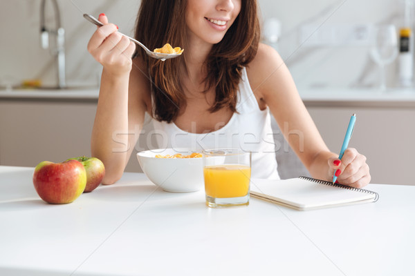 Cropped image of a smiling woman eating cereal Stock photo © deandrobot