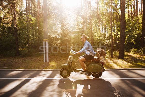 Bearded man on scooter outdoors. Looking aside. Stock photo © deandrobot