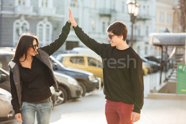 Happy young woman walking outdoors with her brother. Stock photo © deandrobot