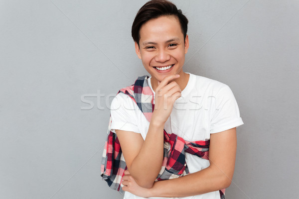 Smiling young asian man over grey background Stock photo © deandrobot