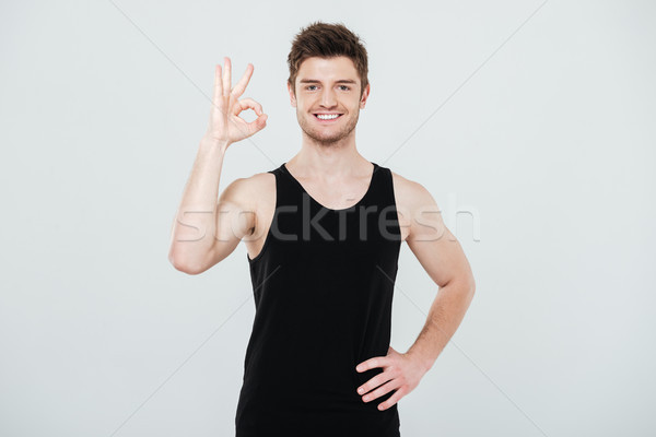 Cheerful young sportsman showing okay gesture. Stock photo © deandrobot