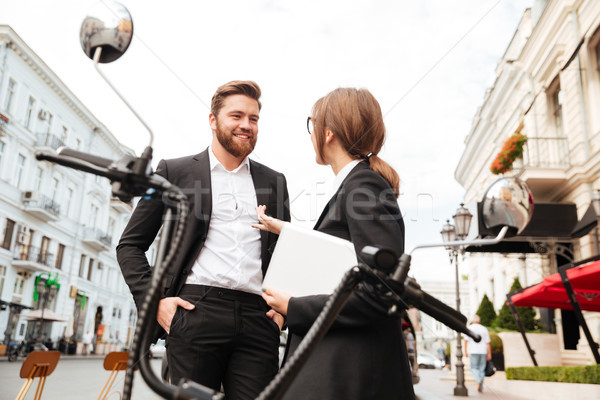 Smiling business couple posing near the modern motorbike outdoors Stock photo © deandrobot