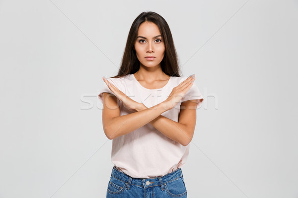 Portrait of a serious concentrated asian woman standing Stock photo © deandrobot