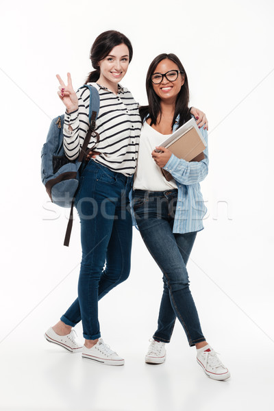 Couple of two happy multiethnic female students with Stock photo © deandrobot