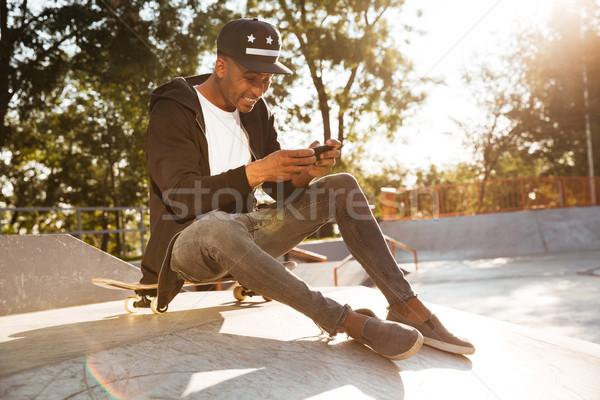 Portré afrikai fickó gördeszkás játszik mobiltelefon Stock fotó © deandrobot