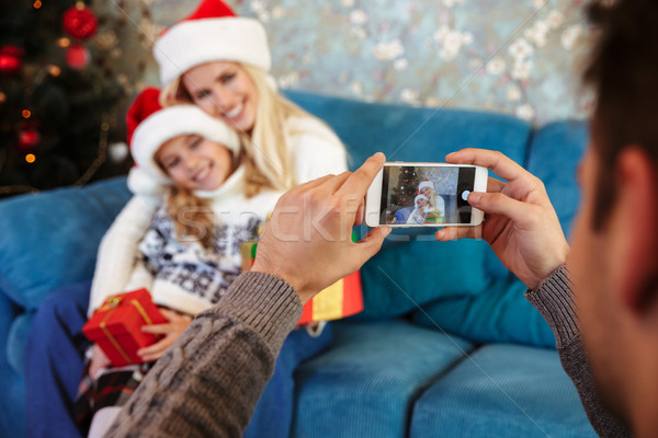 Father taking photo of his cheerful wife and daughter in Santa's Stock photo © deandrobot
