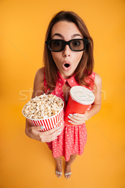 Top view of amazed young woman in 3d glasses holding popcorn and Stock photo © deandrobot