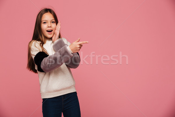 Surprised brunette girl pointing at copy space with opened mouth isolated Stock photo © deandrobot