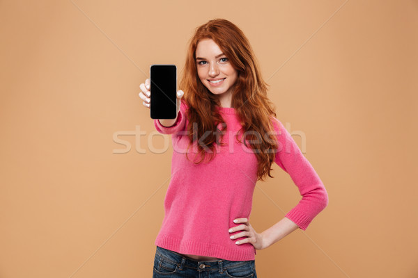 Portrait of a confident attractive redhead girl Stock photo © deandrobot