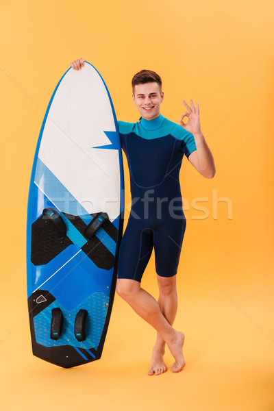 Full length photo of young attractive man in swimsuit holding su Stock photo © deandrobot