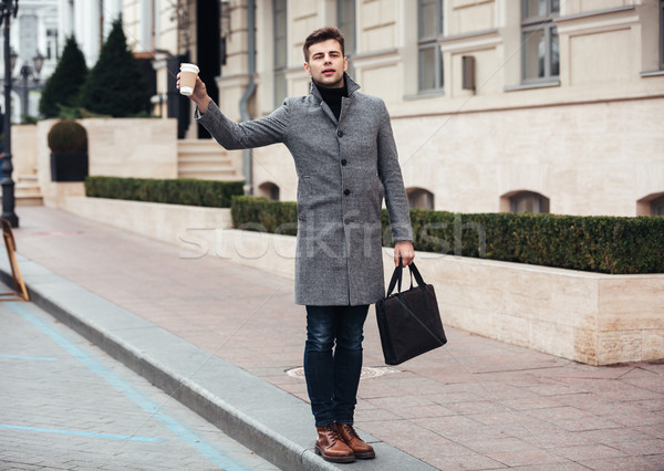 Stylish young man holding takeaway coffee in paper cup, and catc Stock photo © deandrobot