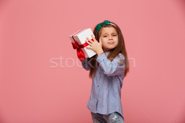 Curious girl 5-6 years shaking present gift-wrapped box close to Stock photo © deandrobot