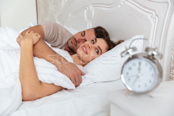 Vista lateral sonriendo Pareja dormir junto cama Foto stock © deandrobot