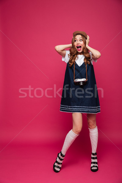 Amazed lady looking aside and smiling while holding retro camera Stock photo © deandrobot
