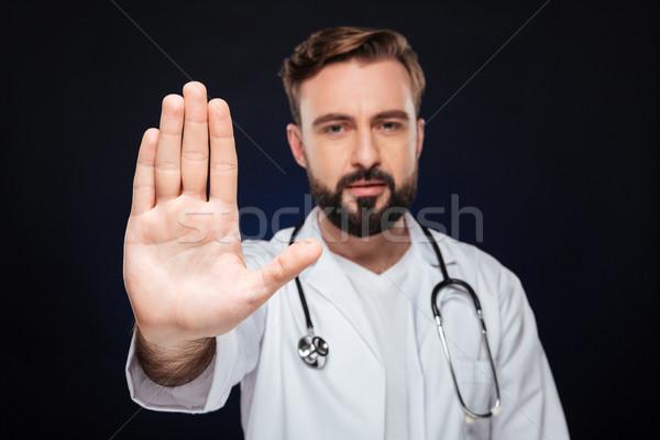 Portrait of a confident male doctor dressed in uniform Stock photo © deandrobot