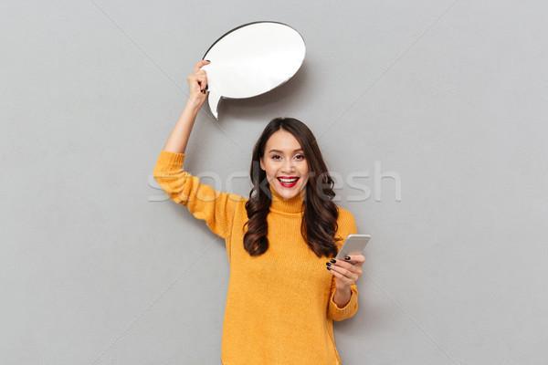 Happy brunette woman in sweater with blank speech bubble overhead Stock photo © deandrobot