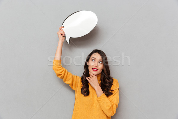 Pensive smiling woman in sweater holding blank speech bubble overhead Stock photo © deandrobot