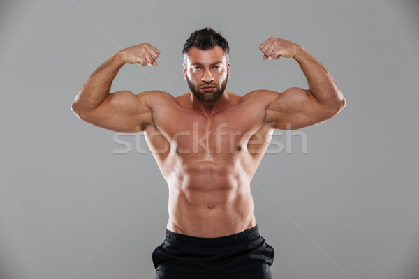 Portrait of a muscular strong shirtless male bodybuilder Stock photo © deandrobot