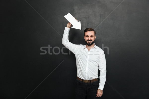 Stock photo: Good-looking brunette man holding blank speech arrow pointer dir