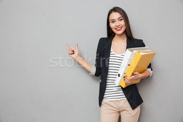 Pleased asian business woman with folders pointing on copyspace Stock photo © deandrobot