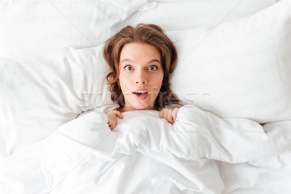 Shocked young woman lies in bed at morning Stock photo © deandrobot