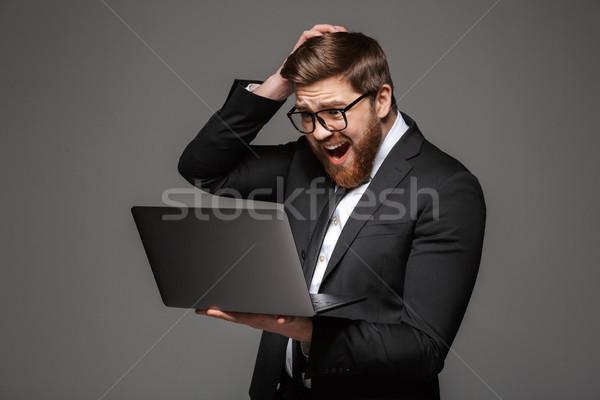 Ritratto deluso giovani imprenditore suit guardando Foto d'archivio © deandrobot