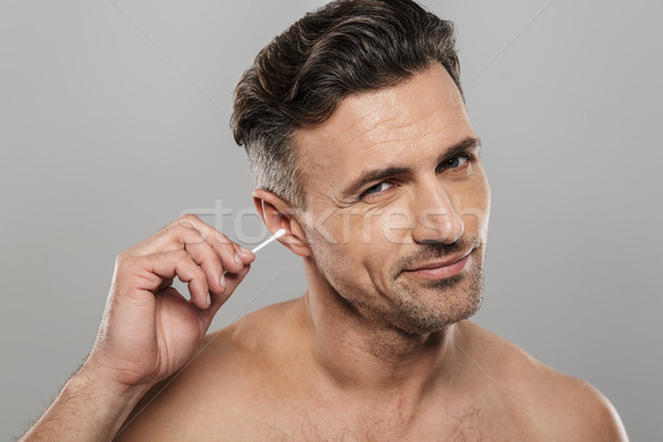 Handsome mature man holding cotton bud take care of his ears cleaning it. Stock photo © deandrobot