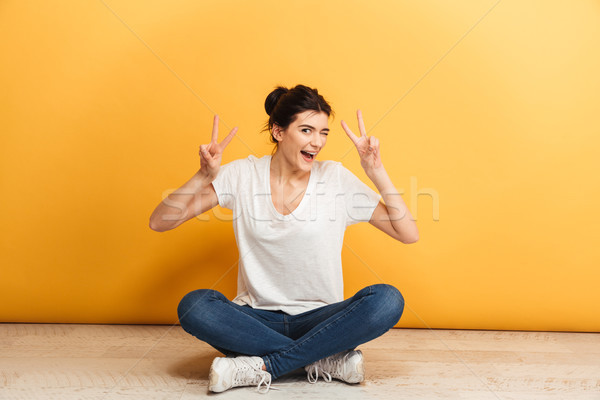 Portrait of a smiling young woman sitting with legs crossed Stock photo © deandrobot