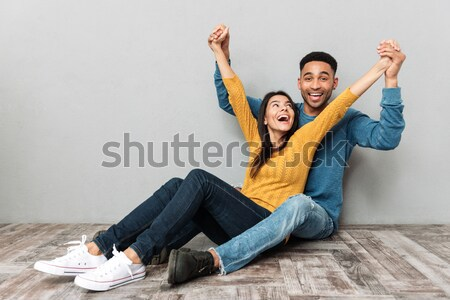 Image of happy two friends man and woman in casual clothing sitt Stock photo © deandrobot