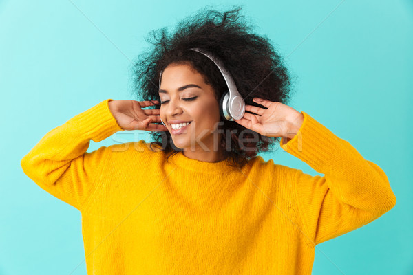 African american glad woman in yellow shirt listening to music v Stock photo © deandrobot