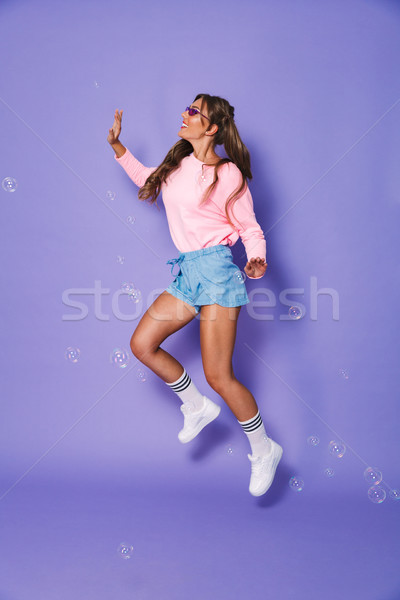 Full length portrait of funny teenage woman with two ponytails i Stock photo © deandrobot