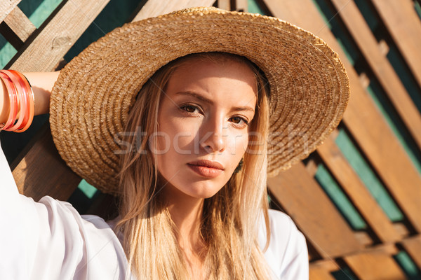 Portrait of attractive young blond woman 20s in straw hat and sw Stock photo © deandrobot