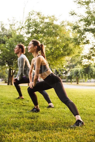 Sport loving couple friends in park outdoors make stretching exercises. Stock photo © deandrobot