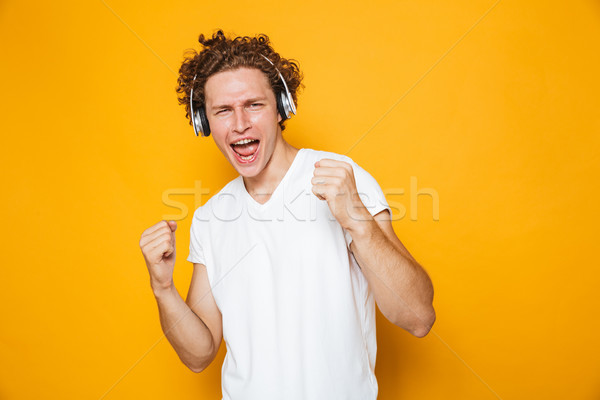Photo of brunette joyous guy with curly hair listening to music  Stock photo © deandrobot
