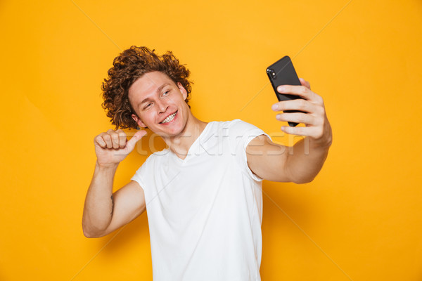 Cheerful man with brown hair pointing finger at himself while ta Stock photo © deandrobot