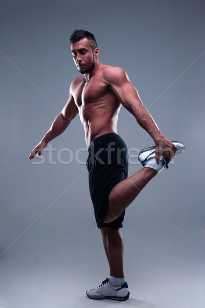 Full length portrait of young man athlete doing stretches exercises  Stock photo © deandrobot