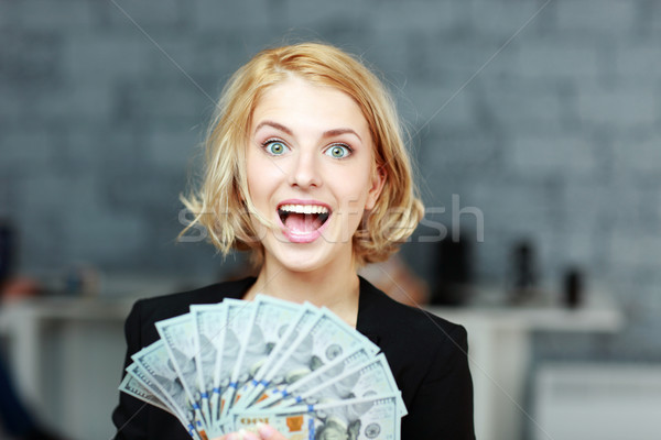 Young businesswoman holding money with delight Stock photo © deandrobot