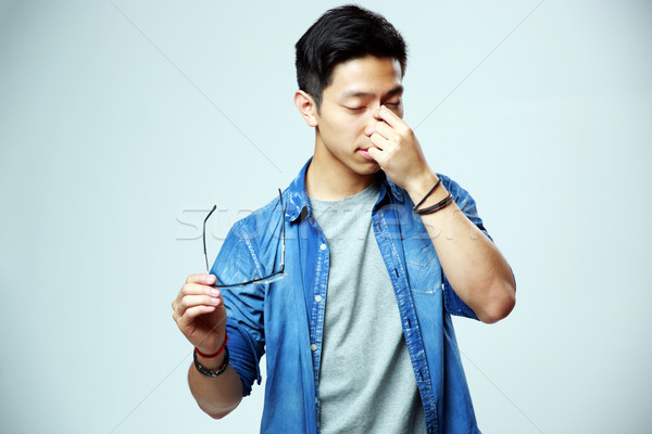 Stock photo: Asian man holding glasses and rubbing his eyes on gray background