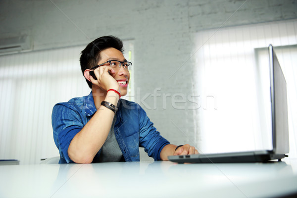 Happy asian man sitting at his workplace in office and talking on the phone Stock photo © deandrobot