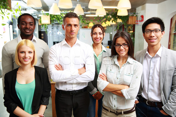 Stock photo: Group of a smiling businesspeople standing together in office