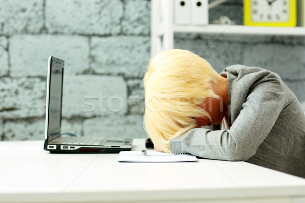 Tired businesswoman sleeping on her workplace in office Stock photo © deandrobot
